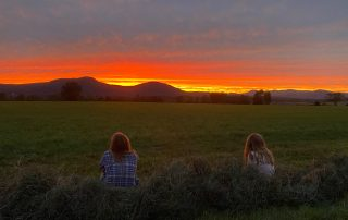 two girls watching sunset over a pasture