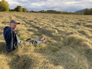 farmer sitting in rows of cut hay