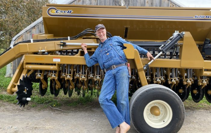 farmer leaning against new no-till tractor